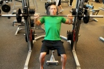 Bryant doing a shoulder press at LA Fitness on the Smith machine