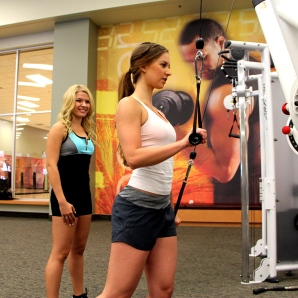 Bailey doing alternating single arm triceps pushdowns - 2