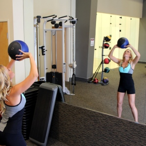 Toni doing a medicine ball shoulder toss at la fitness - 1