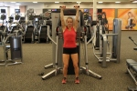 Bethany doing standing cable shoulder presses at LA Fitness 2