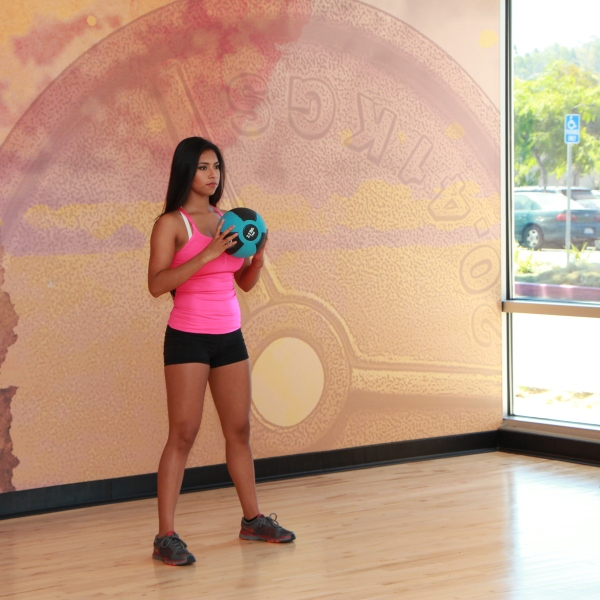 Cynthia-performing-medicine-ball-squat-to-throw-at-LA-Fitness