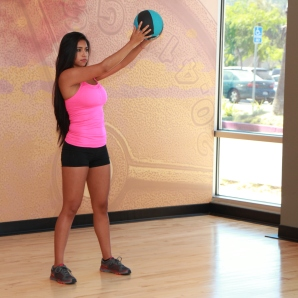 Cynthia-performing-medicine-ball-wood-chop-with-squat-at-LA-Fitness