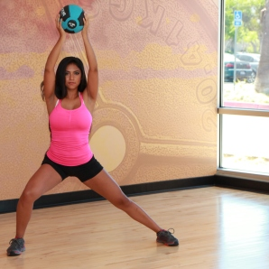 Cynthia-performing-side-lunge-with-shoulder-raise-using-medicine-ball-at-LA-Fitness