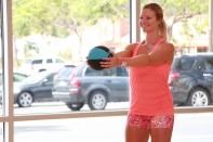 Danica performing a front shoulder raise using a medicine ball at LA Fitness - 2