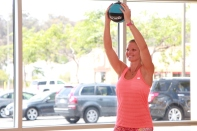 Danica performing a front shoulder raise using a medicine ball at LA Fitness - 3