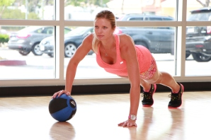 Danica performing single arm medicine ball push-ups at LA Fitness