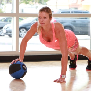 Danica performing single arm medicine ball push-ups at LA Fitness
