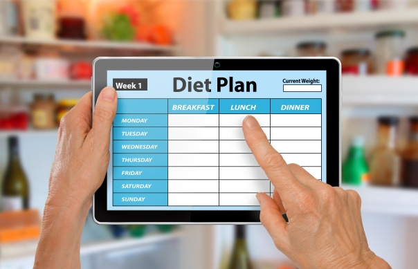 Hands with Tablet Using Diet Plan App in front of open fridge